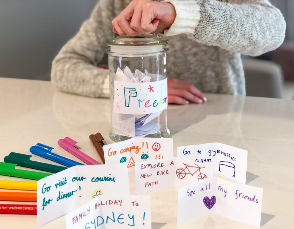 Girl lifting lid on jar of notes